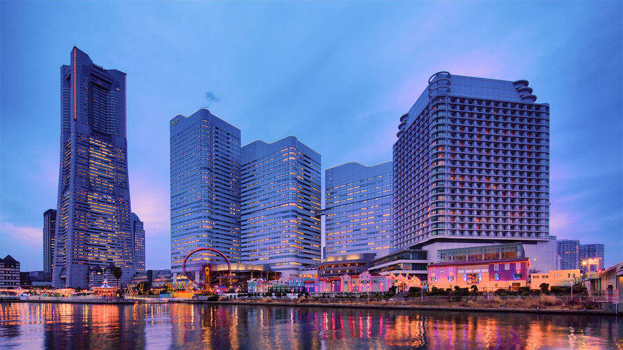 Modern buildings by river against sky in city at dusk