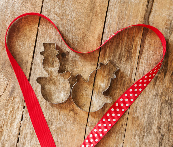 Directly above shot of cookie cutters with ribbon on table