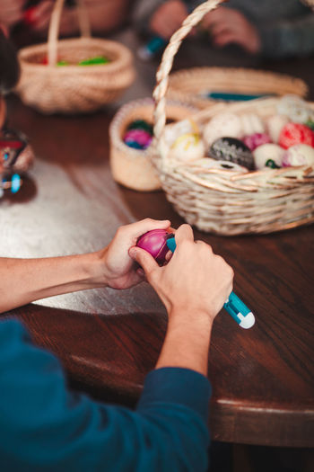 Cropped hands of woman cutting easter egg