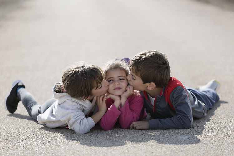 Three children lying on the floor one on top of the other. Horizontal shot with natural light Children Children's Portraits Spanish Tree Children Caucasian Ethnicity Child Childhood Day Looking At The Camera Outdoors People person Smiling Togetherness