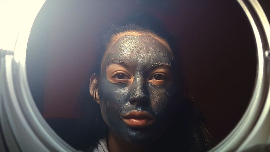 Woman with mud mask reflecting on mirror