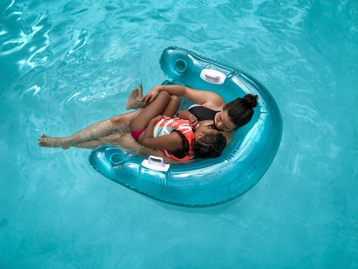 High angle view of woman with girl relaxing on inflatable chair in swimming pool