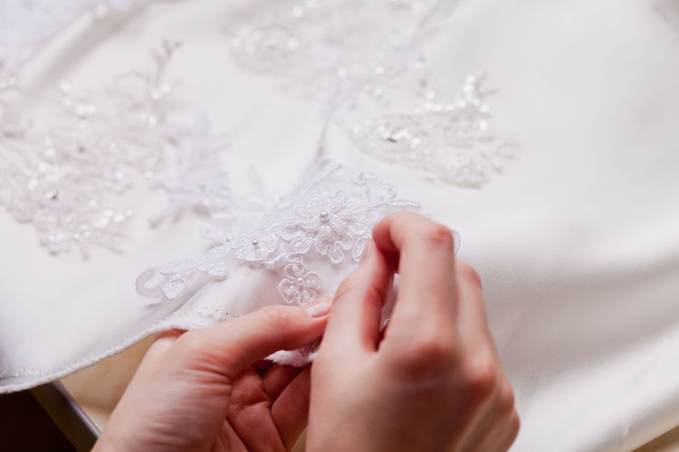Cropped Hands Of Woman Stitching Wedding Dress