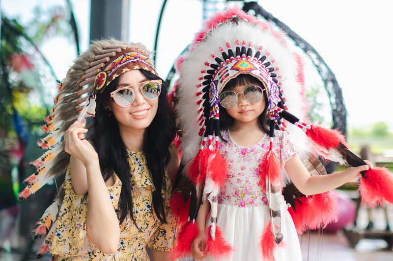 Child Clothing Costume Day Fashion Floral Pattern Focus On Foreground Front View Girls Hairstyle Leisure Activity Lifestyles Looking At Camera Outdoors People Portrait Real People Smiling Standing Women Young Adult Young Women