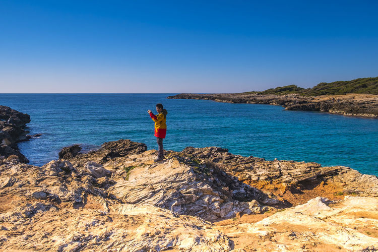 Side view of man standing on rock formation by sea against clear blue sky