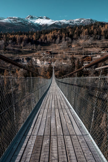 Empty footbridge against snowcapped mountain