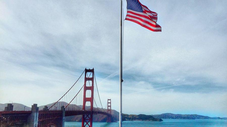 Flag on suspension bridge against cloudy sky