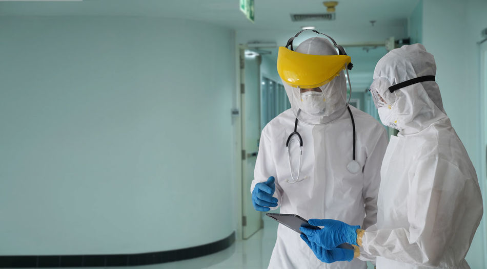 The doctor in the ppe protective suit asked the patient for information to test covid-19 infection.