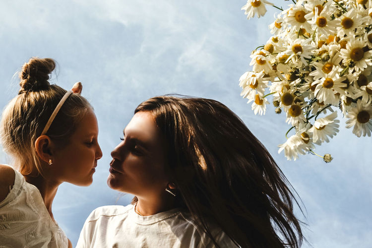 Low angle view of mother kissing daughter by flowers against sky