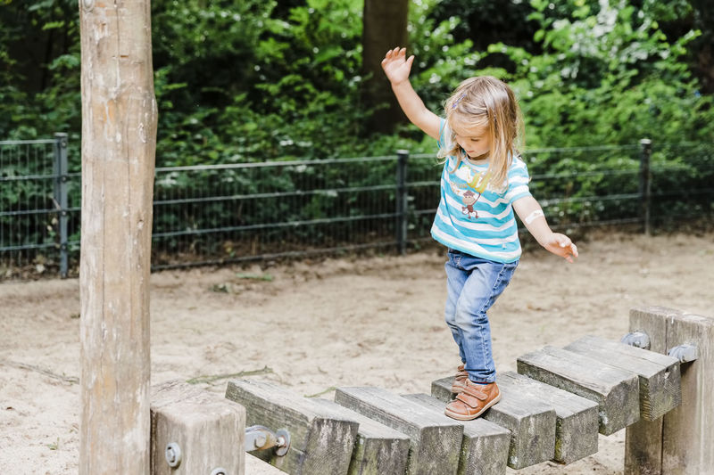 Full length of girl walking on wooden play equipment at playground