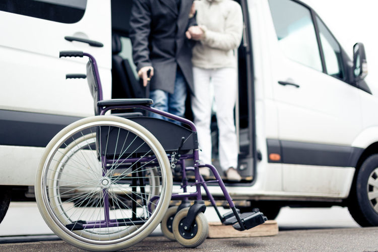 Low Section Of People Standing In Vehicle With Wheelchair In Foreground