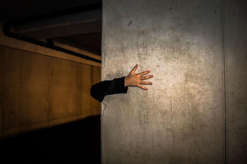 Close-up of man hand on pillar at subway station