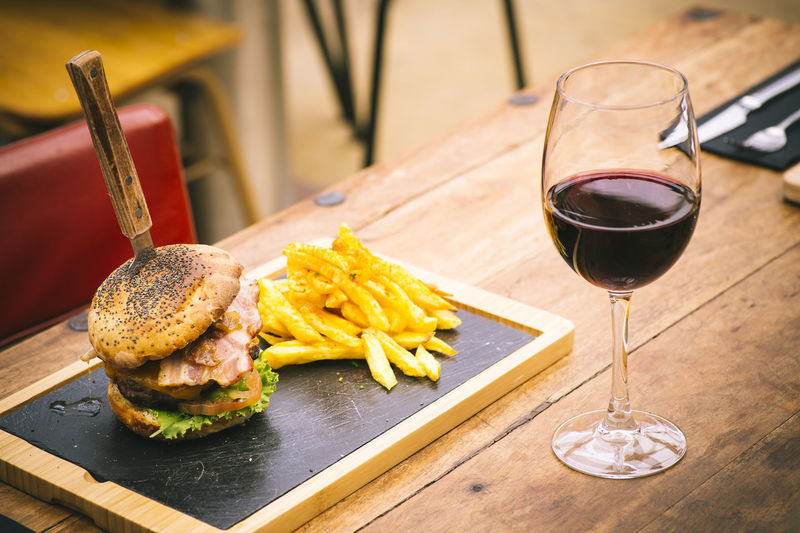 High angle view of french fries and burger by red wine served on wooden table
