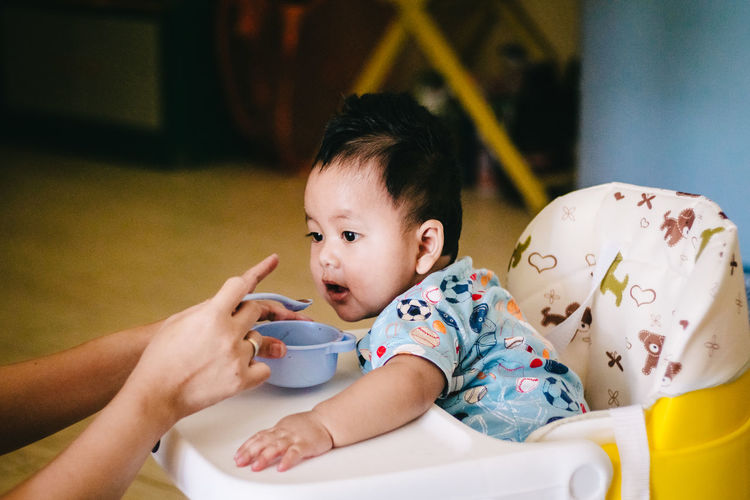 Cropped hands of mother feeding cute baby boy sitting on high chair at home