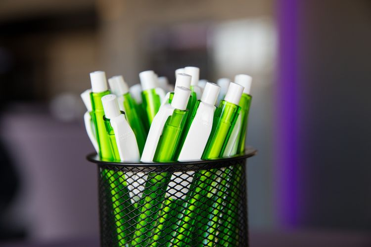 Close-up of green pens in container