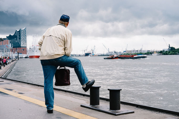 Rear View Of Man Standing On Boat Port With Hand Luggage
