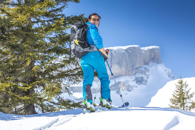 Smiling woman skiing on snow covered field during winter