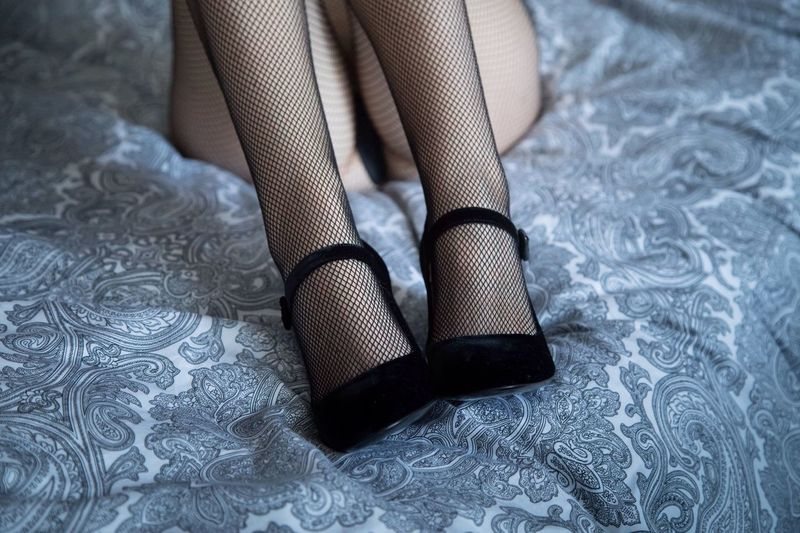 Low section of woman in high heels and stockings on bed