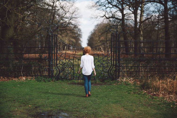 Rear view of young woman on grassy field walking towards closed gate