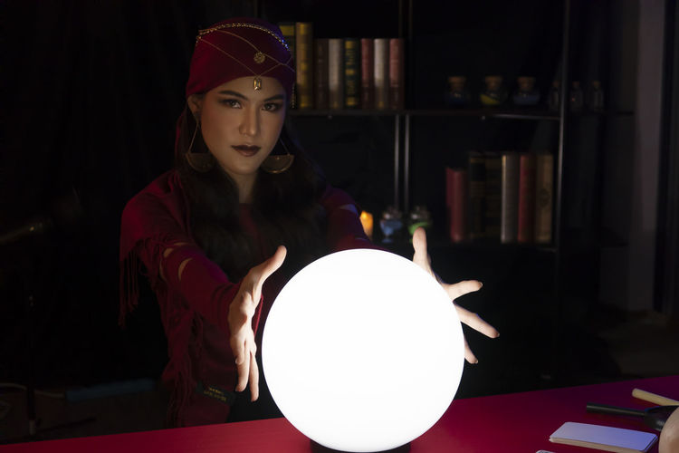 Young woman gesturing over crystal ball while sitting in darkroom