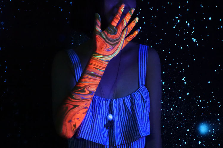 Midsection of woman with multi colored hand standing against illuminated lights at night