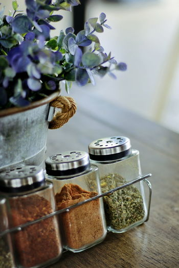 Condiment set with a vase of flowers on the table.