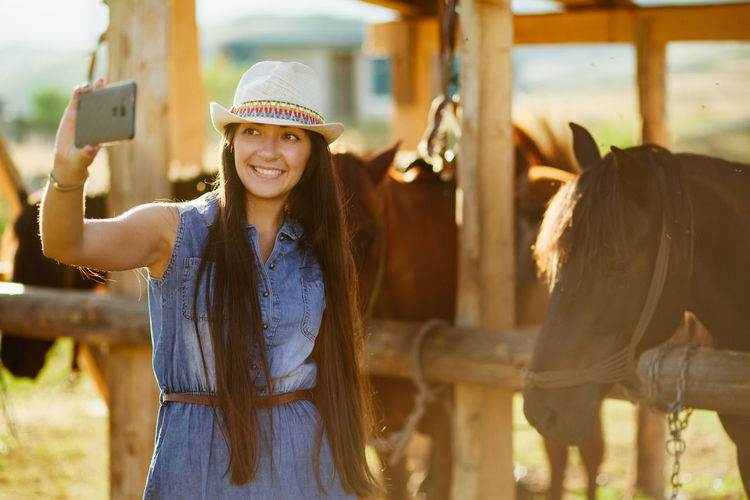 Smiling Young Woman Taking Selfie By Horses At Pen
