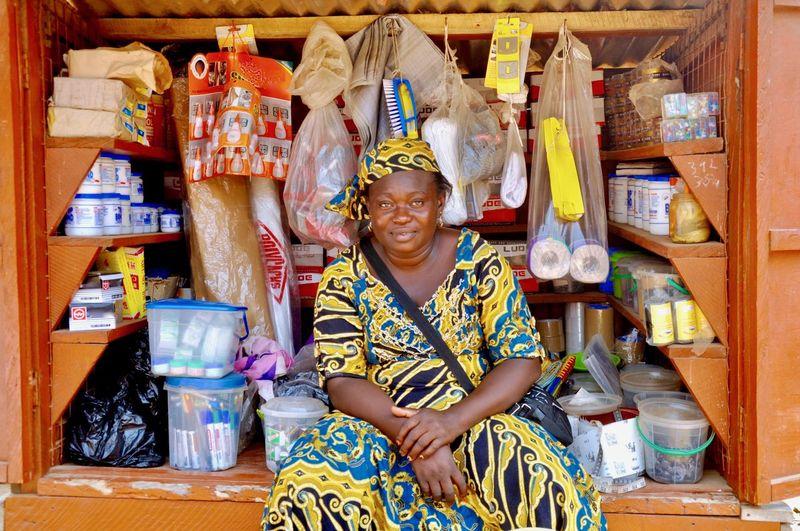 Portrait of female vendor sitting at store