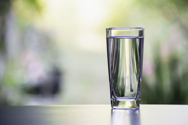 Water in the glass on table with nature background Refreshment Glass Drinking Glass Food And Drink Water Drinking Water Household Equipment Drink Glass - Material Focus On Foreground Transparent Nature No People Day Table Outdoors Close-up Sunlight Single Object Purity Clean