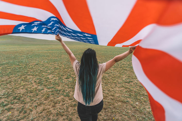 Rear view of woman holding american flag outdoors