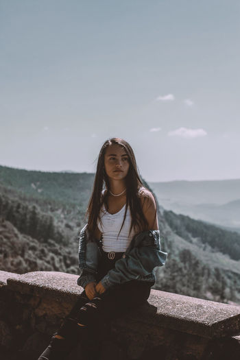 Girl looking away while sitting against sky