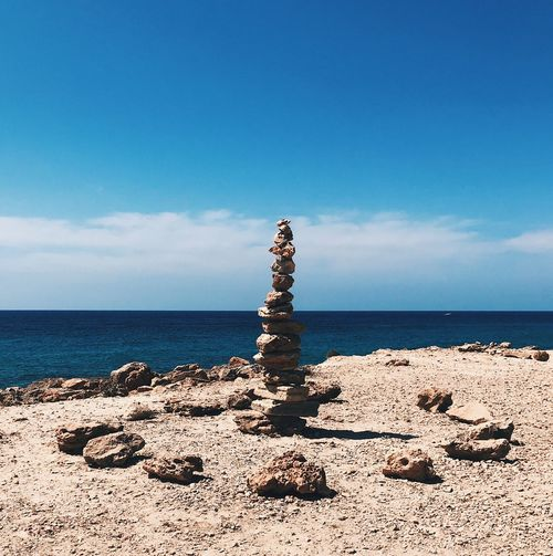 Stones stacked on cliff by sea against sky