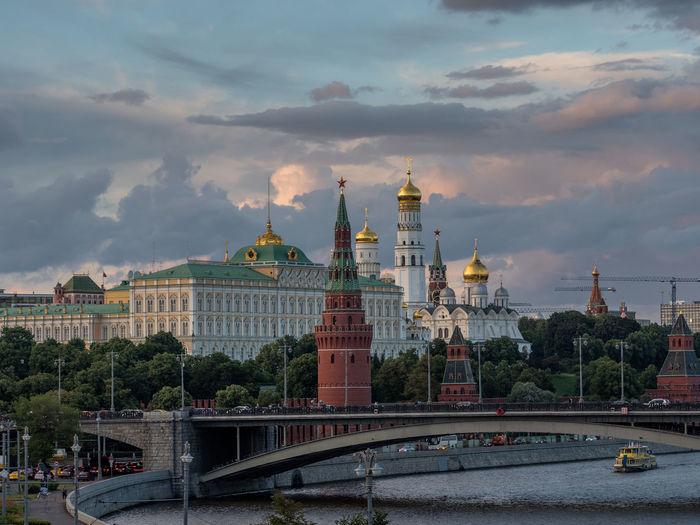 Spasskaya tower by moscva river against cloudy sky