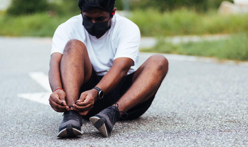 Full length of man tying shoe lace sitting on road
