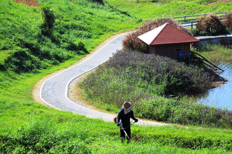 Man walking on road amidst field