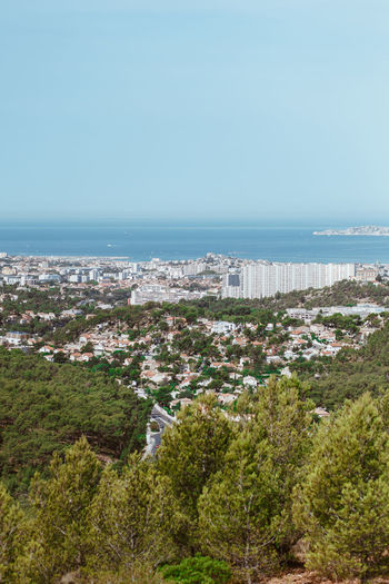 High angle view of cityscape by sea against clear sky