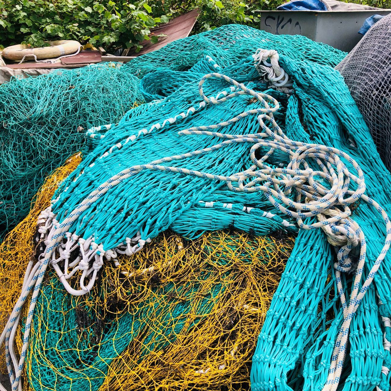 fishing net, commercial fishing net, rope, fishing, day, fishing industry, strength, no people, close-up, complexity, blue, fishing rod, green color, outdoors, high angle view, rod, transportation, netting, pattern, tangled, turquoise colored, fishing boat