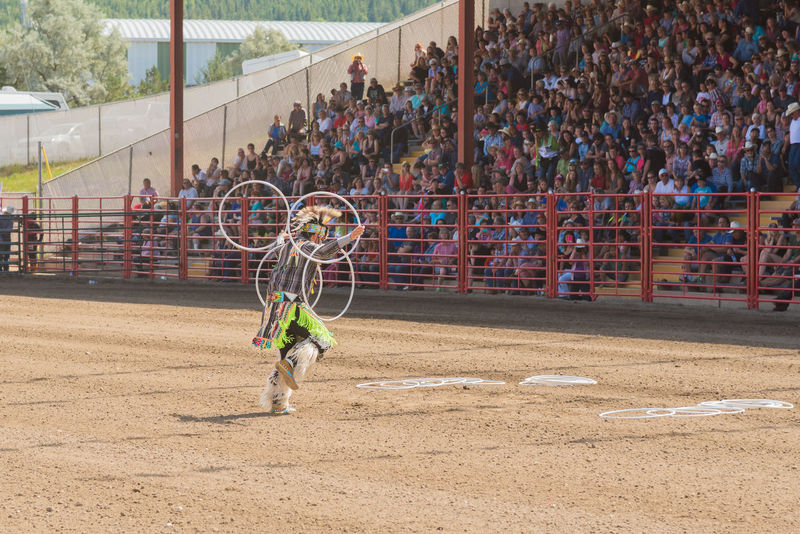 Williams Lake, British Columbia/Canada - July 2, 2016: First Nations hoop dancer Alex Wells, a three time world champion, performs at the 90th Williams Lake Stampede. 90th Williams Lake Stampede Afternoon Alex Wells Arena British Columbia, Canada Dancing First Nations July Man Skill  Tradition Travel Audience Colorful Culture Documentary Editorial  Hoop Dancing Performance Stampede Grounds Stands Summer Talent Tourism World Champion