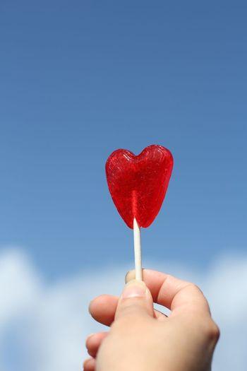 Close-up of hand holding heart shape lollipop against blue sky