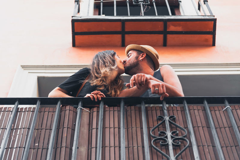 Low angle view of young couple kissing at balcony