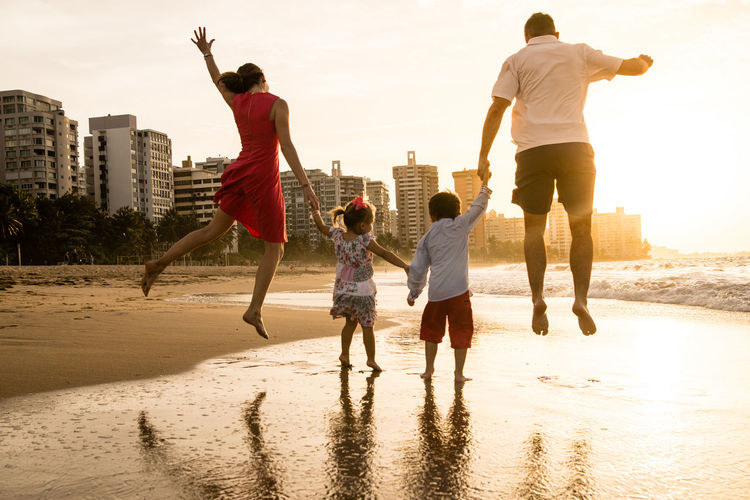 Architecture Beach Bonding Boys Building Exterior Built Structure Childhood City Enjoyment Full Length Fun Leisure Activity Lifestyles Men Mid-air Outdoors Real People Rear View Sand Sky Sunlight Sunset Togetherness Vacations Water