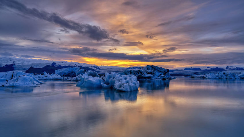 Jökulsárlón is a glacial lagoon, bordering Vatnajökull National Park in southeastern Iceland. Its still, blue waters are dotted with icebergs from the surrounding Breiðamerkurjökull Glacier, part of larger Vatnajökull Glacier. The Glacier Lagoon flows through a short waterway into the Atlantic Ocean, leaving chunks of ice on a black sand beach. Water Sky Glacier Ice Tranquility Scenics - Nature Tranquil Scene Cloud - Sky Environment Cold Temperature Beauty In Nature Reflection Sunset Idyllic No People Frozen Landscape Iceberg Nature Floating On Water Lagoon Melting Global Warming Winter Tourism
