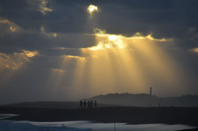 People Standing At Beach Against Cloudy Sky During Sunset