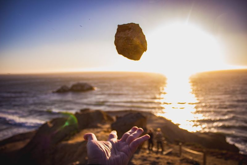 Close-up of person catching rock at beach against sky during sunset