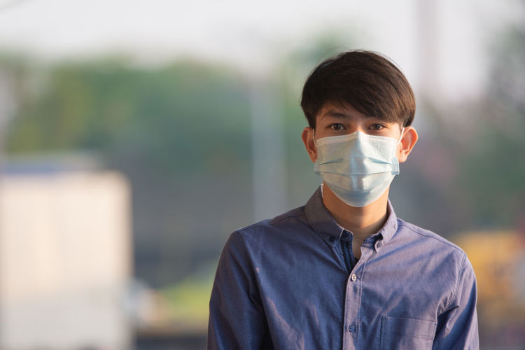 Portrait of teenage boy wearing mask standing outdoors