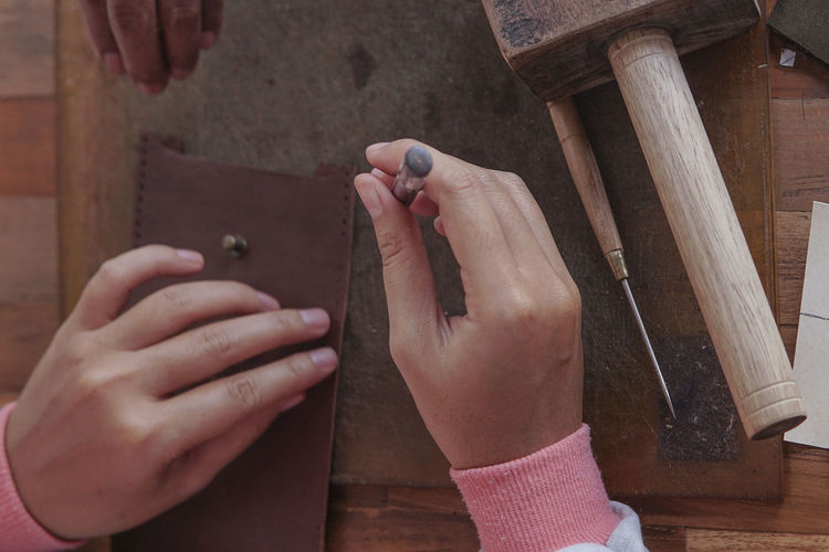 Close-Up Of Hand Making Leather Wallet In Workshop