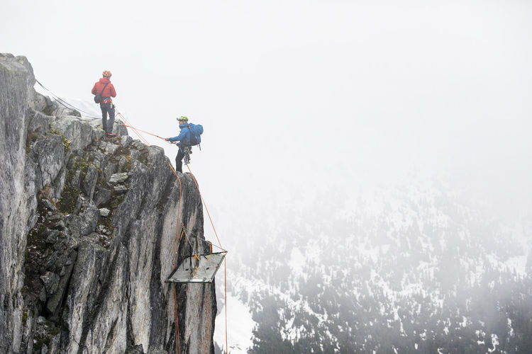 Low angle view of people on mountain against sky