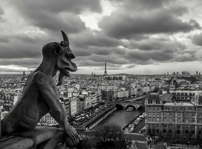 Demon statue and residential district against cloudy sky