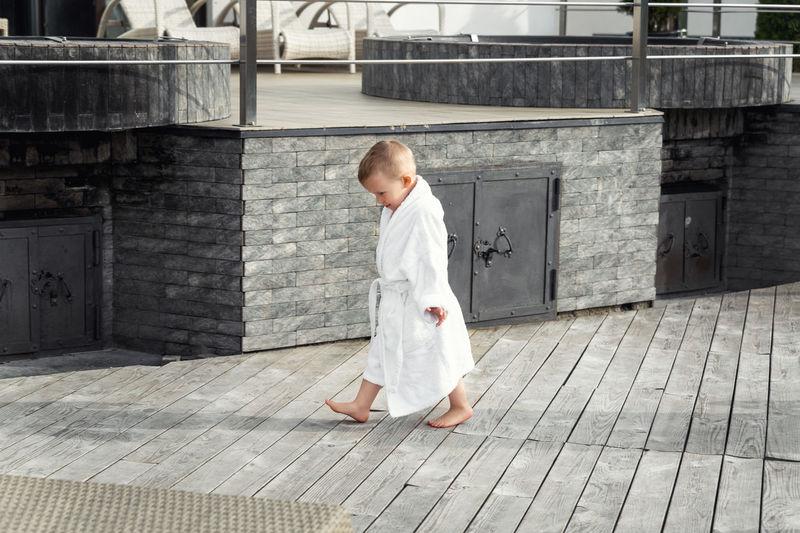 Full length of girl walking on footpath against building