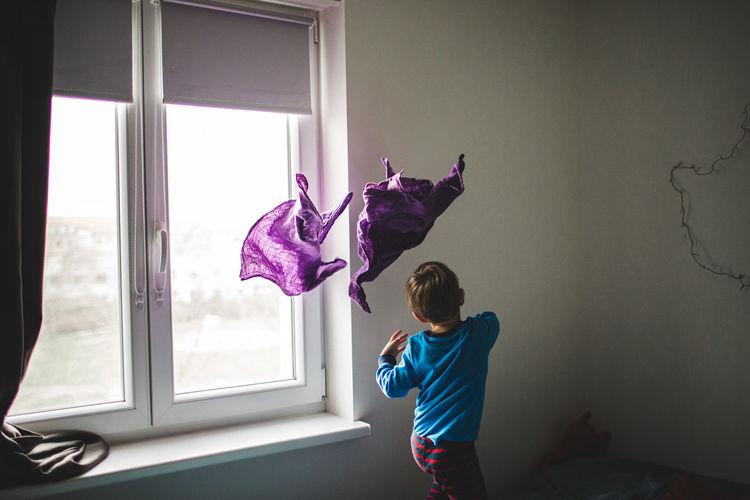 Boy throwing fabrics in room